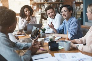 People together talking and listening at a table. Salesforce social media monitoring solutions, equip you to monitor what customers are saying about you. See how Venerate can help.