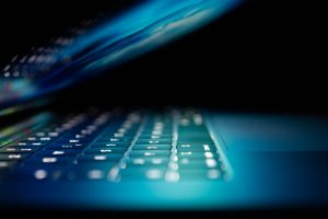 Laptop opening, focused on keyboard. Venerate Solutions are experts in implementing digital transformation services in hi-tech and technology companies. Click to find out more.